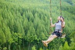 Joyful woman playing on swing Royalty Free Stock Photo