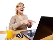 Joyful woman pointing at laptop screen Stock Image