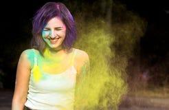Joyful woman with purple hair having fun with dry Holi powder S Стоковые Фото