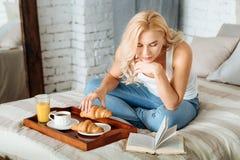 Joyful woman reading book in bed Stock Image