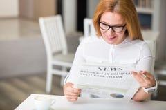 Joyful woman reading newspaper Royalty Free Stock Image