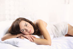 Joyful woman resting in a soft, white linen Stock Photos