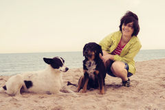 Joyful woman rests with a dogs. On the beach. Toned image Stock Photo