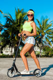 Joyful woman riding a kick scooter near palms in tropical country. Caucasian model with long hair Stock Photography