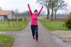 Joyful woman running and leaping. Joyful athletic fit woman running and leaping along a country road in winter with her arms raised and a beaming smile Stock Photos