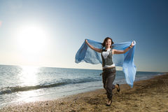 Joyful woman running at sea shore Royalty Free Stock Photography