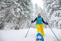 Joyful woman runs on snowshoes through the coniferous forest Royalty Free Stock Photos