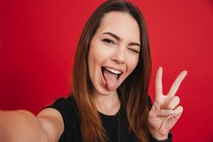 Joyful woman 20s with long brown hair having fun and taking self. Ie with gesturing victory sign isolated over red background Royalty Free Stock Images