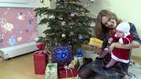 Joyful woman show her lovely baby gift box near Christmas tree stock video footage