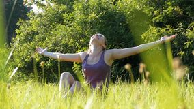 Joyful woman sitting on the green lawn happily lifts her hands up to the sky on scenic field at sunset background stock video