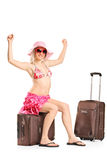 Joyful woman sitting on her baggage Royalty Free Stock Photo