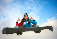 Joyful woman snowboarder sitting on top of mountain on blue sky Stock Photos