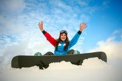Joyful woman snowboarder sitting on top of mountain on blue sky Stock Image