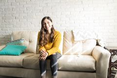 Joyful Woman Spending Time Alone At Home. Portrait of fashionable woman smiling while sitting on couch royalty free stock photo