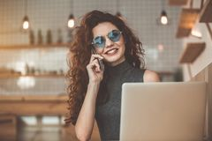 Joyful woman talking on mobile phone in coffee shop. Portrait of charming young girl speaking by smartphone and laughing. She is resting in cozy cafeteria Royalty Free Stock Images