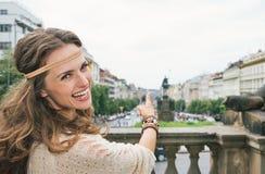Joyful woman tourist pointing on Saint Wenceslas statue, Prague Royalty Free Stock Image