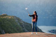 Joyful woman travel and photo selfie. In mountains. Picturesque location in Montenegro, Europe Royalty Free Stock Photos