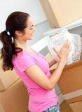 Joyful woman unpacking boxes with glasses Stock Photography