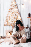Joyful woman unpacking Christmas gifts. Joyful girl in a white knit sweater unpacking Christmas gifts. Bright Christmas background is made of eco-friendly Stock Photo