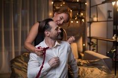 Joyful woman untying bow of ardent man in bedroom stock photos