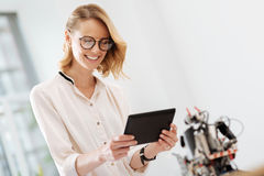 Joyful woman using innovative gadgets in the office Royalty Free Stock Images
