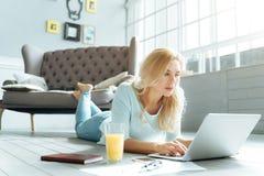Joyful woman using laptop in living room Stock Photo