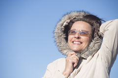 Joyful Woman warm winter jacket outdoor. Portrait happy attractive mature woman wearing warm winter jacket with hood and sunglasses, joyful smiling with blue sky Royalty Free Stock Photography