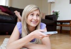 Joyful woman watching TV lying on the floor Stock Image