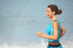 Joyful woman wearing sporty clothers is running. Royalty Free Stock Images