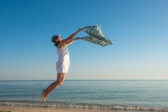 Joyful woman in a white dress is jumping in a deserted beach Stock Photography