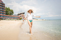 Joyful woman in white shirt walking on the beach at sunny day Stock Photos