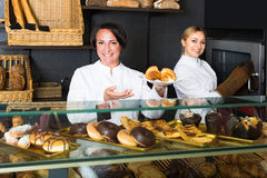 Joyful woman and young girl suggesting pastry Royalty Free Stock Photos