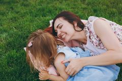 Joyful woman in light dress and little cute child baby girl lie on green grass in park rest, play and have fun. Mother. Joyful women in light dress and little stock photo