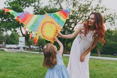 Joyful woman in light dress and little cute child baby girl play with colorful kite on grass in green park. Mother royalty free stock photos