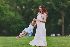 Joyful woman in light dress and little cute child baby girl playing circling around on green grass lawn in park. Mother. Joyful women in light dress and little stock images