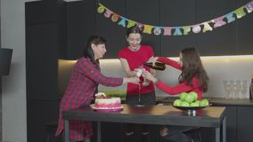 Female guest opening champagne at birthday party. Joyful women opening bottle of champagne and pouring sparkling drink into glasses on occasion of festive event stock video footage