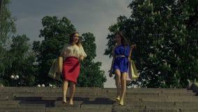 Joyful women with shopping bags going downstairs stock video