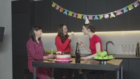 Joyful women toasting, laughing at birthday party. Happy woman in party hat receiving birthday greetings from friend guest during celebration in decorated stock footage
