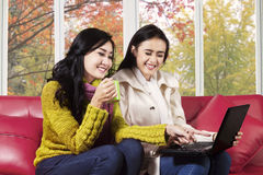 Joyful women using laptop on sofa Stock Photo