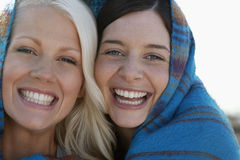 Joyful Women Wrapped In Blanket Stock Photo