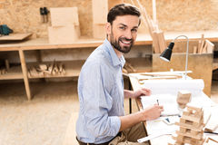 Joyful woodworker is laboring with pleasure in workshop Royalty Free Stock Photo
