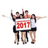 Joyful workers with goals for 2017. Picture of a joyful businesspeople holding a whiteboard with business goals for 2017, isolated on white background Stock Photos