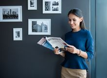 Pleasant elegant girl is enjoying journal. Joyful working time. Optimistic stylish young woman is standing with business magazine and reading with pleasure. She royalty free stock photos