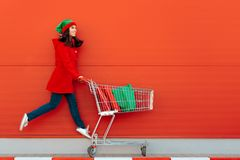 Happy Woman with Shopping Cart Ready for Christmas Sale stock photo