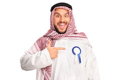 Joyful young Arab with an award ribbon. Joyful young Arab wearing an award ribbon on his robe and pointing towards it with his hand isolated on white background Royalty Free Stock Image