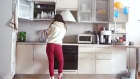 Joyful young beautiful woman is dancing in kitchen wearing pajamas and headphones drinks a cup of coffee in the morning