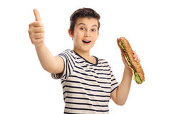 Joyful young boy holding a sandwich and giving a thumb up Royalty Free Stock Images