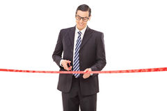 Joyful young businessman cutting a red ribbon Stock Images