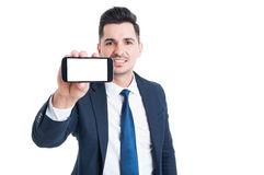 Joyful young businessman holding smartphone with blank screen Stock Photo