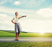 Joyful young businesswoman pointing. At something and laughing Royalty Free Stock Images